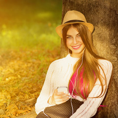 Young woman with smartphone and earphones in park
