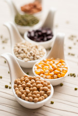 Different kinds of bean seeds, lentil, peas in dish on wooden ta
