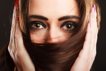 Closeup woman covers the face by long brown hair