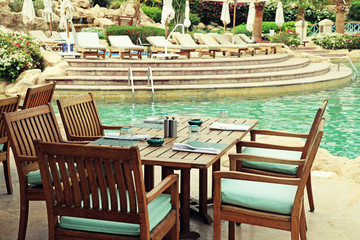 Table and chairs in outdoor cafe next to the resort swimming poo