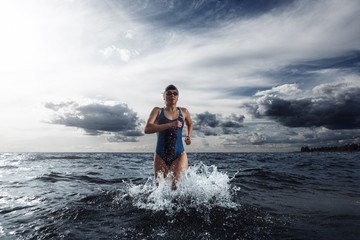 Young woman athlete running out of water