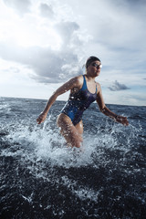 Young woman athlete running out of the water