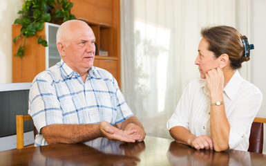 mature couple having serious talking at home
