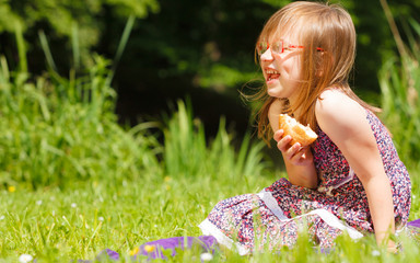 Funny playful little girl having picnic in park