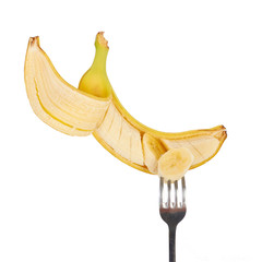 Banana and ripe piece prick with a fork isolated on white