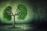 green tree shaped like human lungs growing from concrete floor