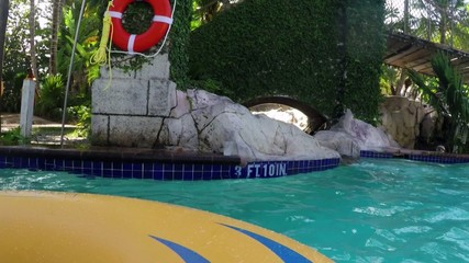 Floating down lazy river at water park tropical vacation resort