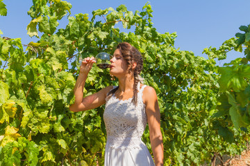 Young woman farmer tastes a glass of red wine.