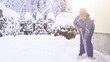 Young woman shoveling snow near the house after intense snowfall