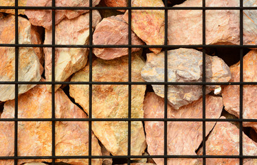 A volcanic stone and steel net fence texture