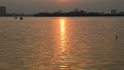 Zoom Out - Time Lapse of Golden Sunset Reflections on a Lake in Hanoi Vietnam