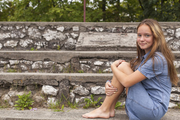Cute young girl sitting on the stone steps at the old city Park.