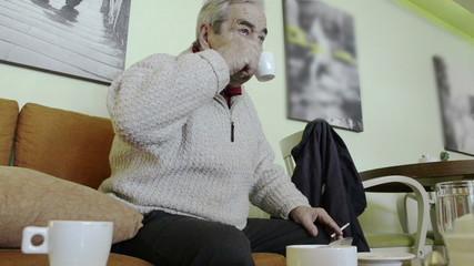 Elderly man drinking coffee in a cafe