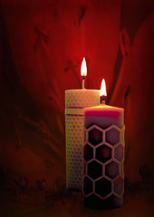 Two beeswax candles flame on a red background