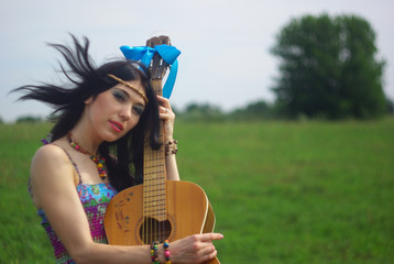 Hippie posing outdoor with guitar. Boho-chic. Boho style.