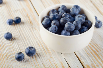 Blueberries in a bowl on  wooden table.