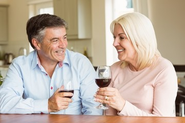 Happy mature couple drinking red wine