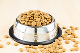 Dog Kibbles in a bowl on wooden floor poster