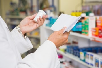 Pharmacist reading prescription and holding medicine