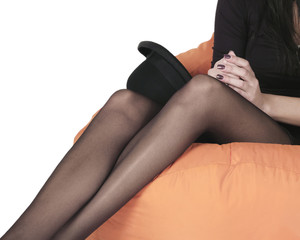 sexy legs of young woman sitting with black pantyhose