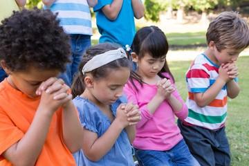 Children saying their prayers in park