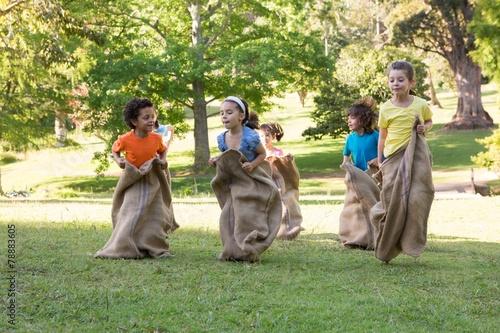 Children having a sack race in park - 78883605