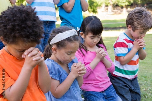 Children saying their prayers in park - 78883616