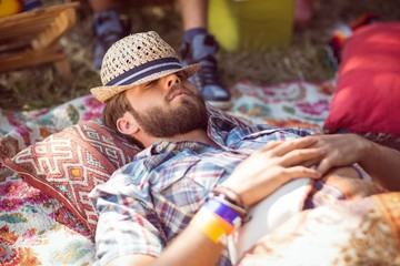 Handsome hipster relaxing on campsite
