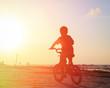 little boy riding bike at sunset - 78884869