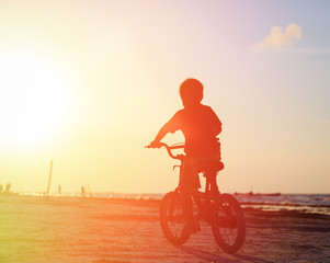 little boy riding bike at sunset