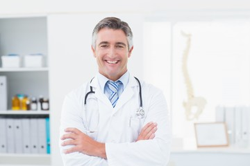Confident doctor with arms crossed standing in clinic
