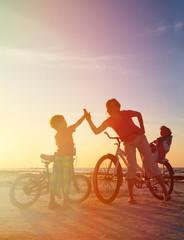 Biker family silhouette at sunset