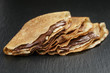 thin crepes or blinis with chocolate cream on slate board - 78885451
