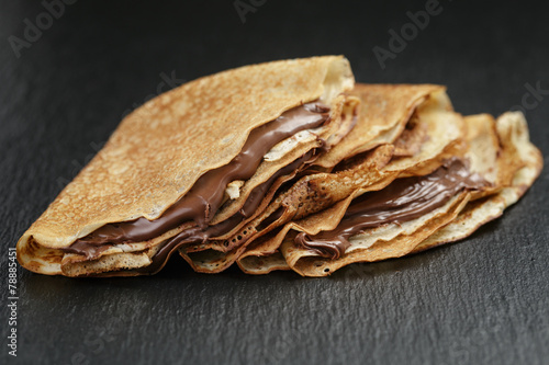 Poster Dessert thin crepes or blinis with chocolate cream on slate board