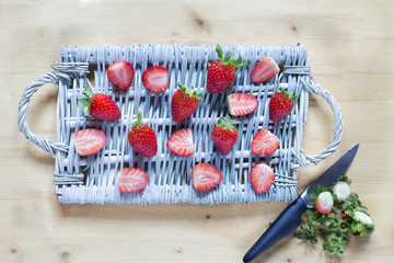 Fresh strawberry on a wicker tray and the rests with knife