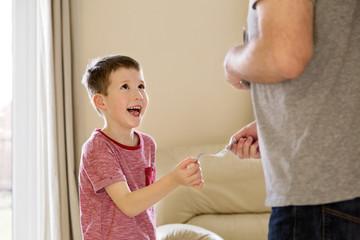 Boy receiving pocket money (allowance) from father