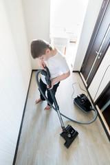 Kid using vacuum cleaner in  house