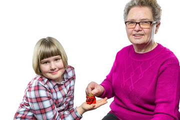 Grandmother putting euro coin in grandchild's piggy bank