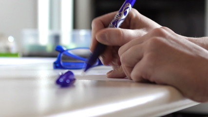 Woman hands taking a blue pen and writing a note it in a office