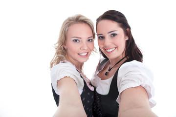 Freundinnen im Dirndl machen Selfie mit Handy