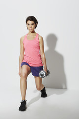 Agile woman lunging weights