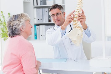 Doctor explaning anatomical spine to female patient