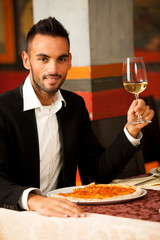 Handsome Man eating pizza in restaurant