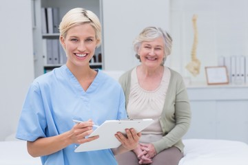 Nurse holding clipboard while female patient sitting in clinic