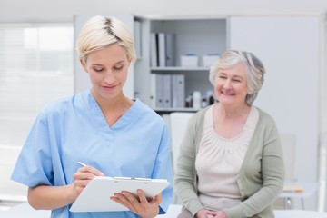 Nurse writing on clipboard while patient sitting in clinic