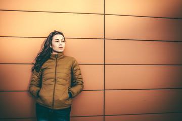 Girl on the city street near wall