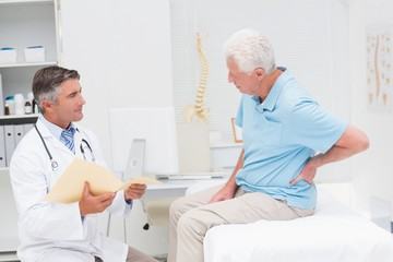 Doctor discussing reports with patient suffering from back pain