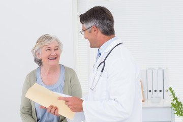 Doctor and patient conversing over reports