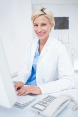 Confident female doctor using computer in clinic