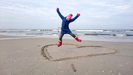 Young girl jumping on the beach over a heart drawn in the sand